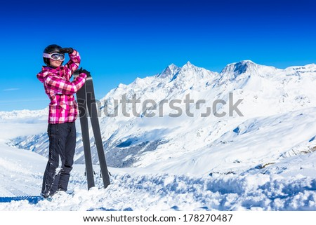 Happy woman in ski goggles against wonderful winter mountains background - stock photo