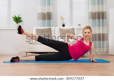 Happy Woman In Sportswear Exercising In Living Room At Home - stock photo