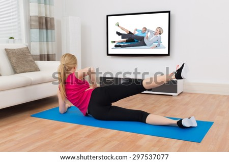 Happy Woman In Sportswear With Exercise Mat Exercising In Front Of Television In Living Room - stock photo