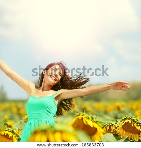 Happy woman in sunflower field. Summer girl in flower field cheerful and joyful. Multiracial Asian Caucasian young woman dancing, smiling elated and serene with arms raised up. - stock photo