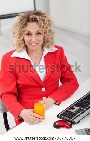 Happy woman in the office with a glass of juice - stock photo