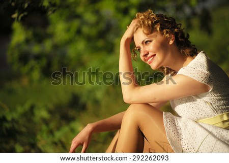 Happy woman in white dress sitting on green grass in summer park - stock photo