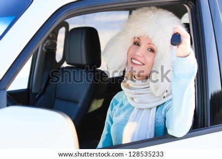 Happy woman in white fur hat in a car showing a key - stock photo