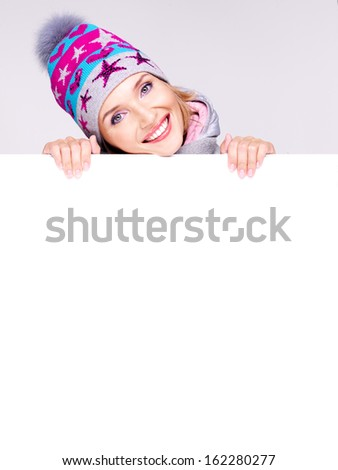 Happy  woman in winter outerwear over white banner in hands at studio - stock photo