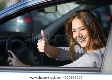 Happy woman inside a car driving in the street and gesturing thumb up - stock photo