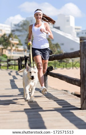 happy woman jogging with her dog - stock photo