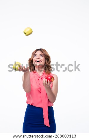 Happy woman juggles with apples isolated on a white background - stock photo