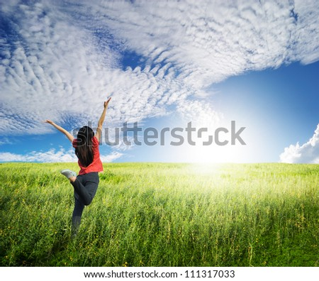 Happy woman jump in grass fields and blue sky - stock photo
