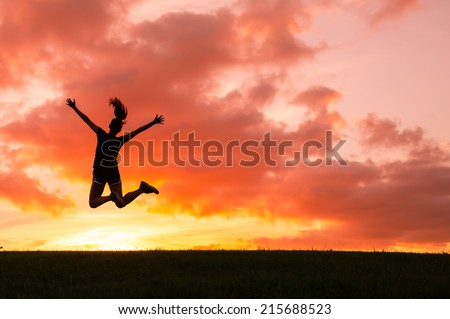 Happy woman jumping against beautiful sunset. Freedom, enjoyment concept. - stock photo