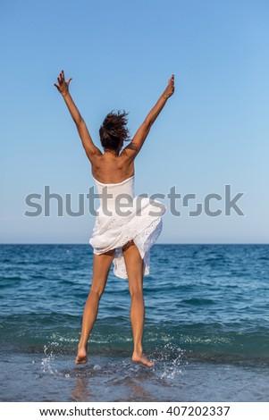 Happy woman jumping at the sea coast. - stock photo