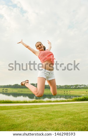 Happy woman jumping expressing winning, success, excitement, and fun lifestyle - stock photo