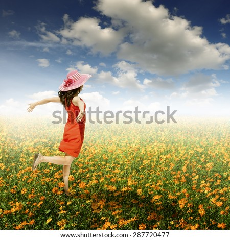 Happy woman jumping in cosmos flower field and blue sky.Summer holiday concept. - stock photo
