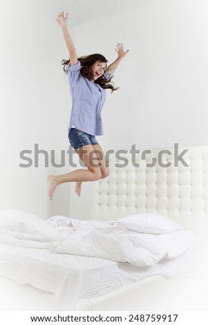 Happy woman jumping on her bed - stock photo