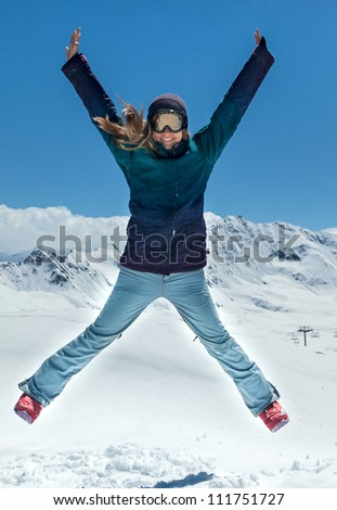 Happy woman jumping on the background of snowy mountains - stock photo