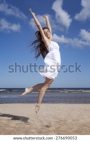 Happy woman jumping on the beach - stock photo