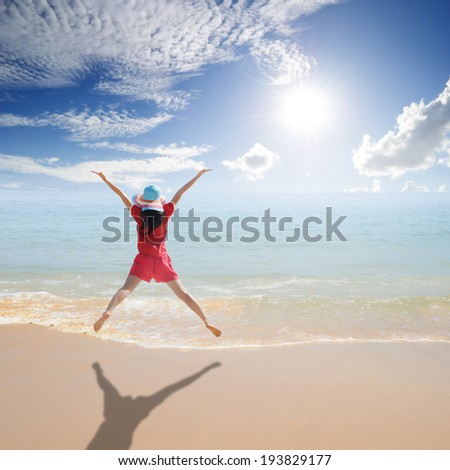 Happy Woman jumping on the beach and sun sky - stock photo