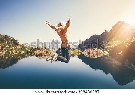 Happy Woman jumping up Flying levitation with lake and mountains on background Lifestyle Travel emotions concept outdoor  - stock photo