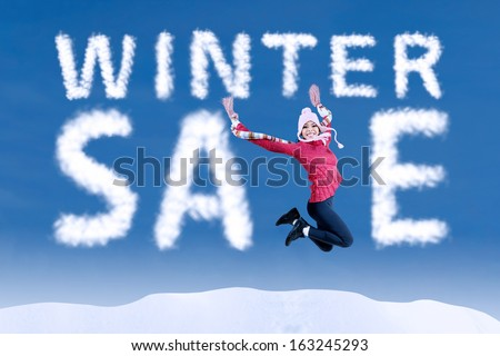 Happy woman jumping with a winter sale sign on blue sky - stock photo