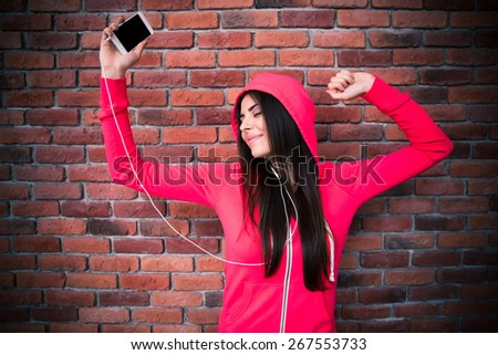 Happy woman listening music and dancing in headphones over brick wall - stock photo