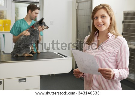 Happy Woman Looking At Bill In Veterinary Surgery - stock photo