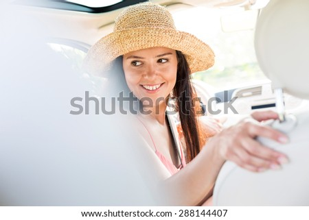 Happy woman looking back while driving car - stock photo