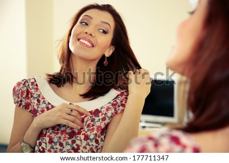 Happy woman looking on her reflection in the mirror at home - stock photo