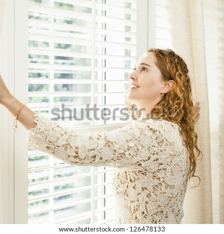 Happy woman looking out big bright window with curtains and blinds - stock photo