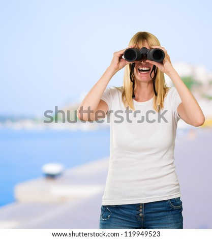 happy woman looking through binoculars at a port - stock photo