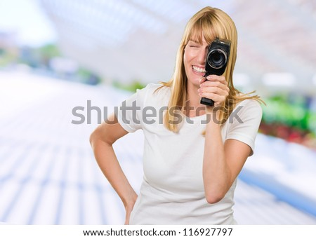 Happy Woman Looking Through Camera outside on the street - stock photo