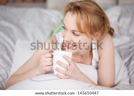 Happy woman lying in bed while drinking coffee - stock photo