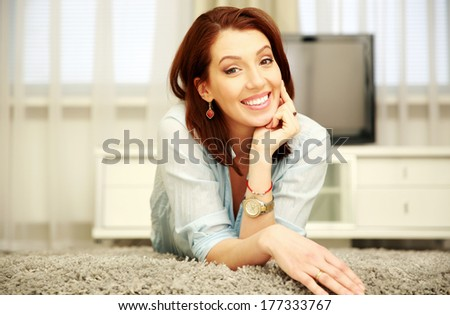 Happy woman lying on the floor at home - stock photo
