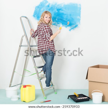 Happy woman makes repairs at home - painting wall at room. - stock photo