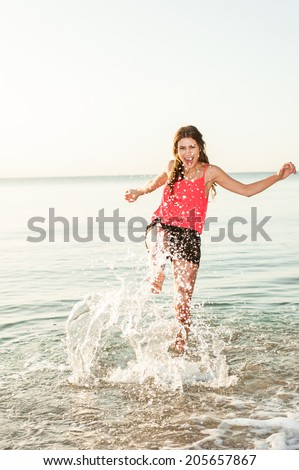 Happy woman making splashes on the beach at sunrise - stock photo
