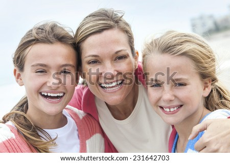 Happy woman mother and her female girl children having fun together laughing and smiling on vacation at a beach - stock photo