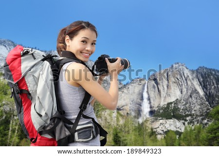 Happy woman mountain hiker taking pictures in Yosemite waterfall, California, USA, asian beauty - stock photo