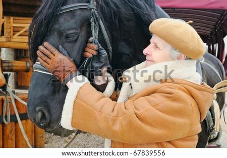 happy woman near black horse; outdoor - stock photo