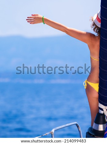 Happy woman on sailboat, back side of cheerful girl with raised up hand enjoying majestic seaview, summer vacation concept  - stock photo