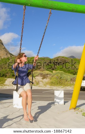Happy woman on swings on beach among awesome mountains. Shot in Hermanus, Walker Bay, Western Cape, South Africa. - stock photo