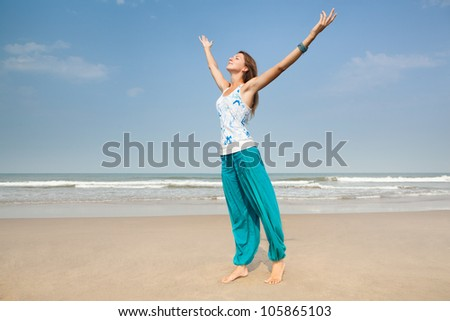 Happy woman on the beach arms stretched - stock photo