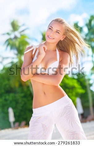 Happy woman on the beach posing with beautiful starfish, enjoying active summer vacation on exotic island, pleasure and wellness concept - stock photo