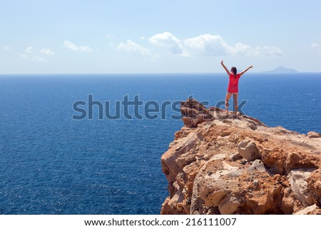 Happy woman on the rock with hands up. Winner, success, active, travel concepts. Santorini island, Greece. Winner, success, active, travel concepts - stock photo