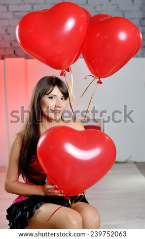 happy woman on Valentine's Day with red balloons in the shape of heart. - stock photo