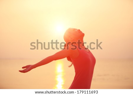 happy woman open arms under the sunrise at sea  - stock photo