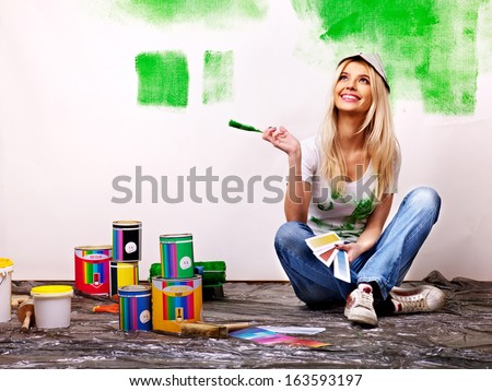 Happy woman paint wall at home. - stock photo
