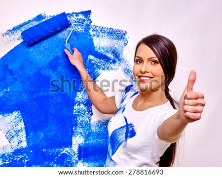 Happy woman paint wall at home and showing thumb up. - stock photo