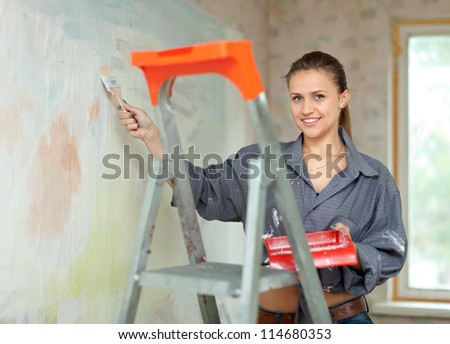 Happy woman paints wall with brush - stock photo