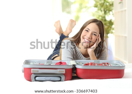Happy woman planning a travel preparing a suitcase and looking at camera - stock photo