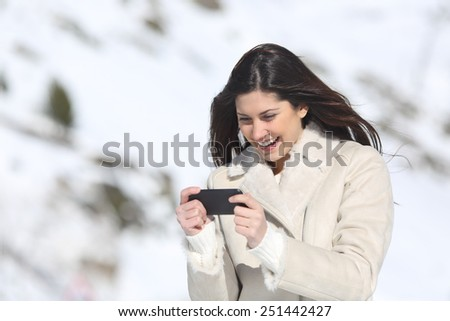 happy woman playing games in a smart phone on winter holidays with a snowy mountain in the background - stock photo