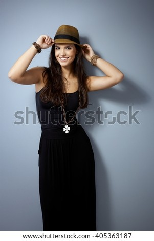 Happy woman posing in straw hat and black dress over grey wall, looking at camera. - stock photo