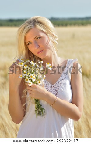 Happy woman posing in white dress with camomile  in golden wheat. - stock photo